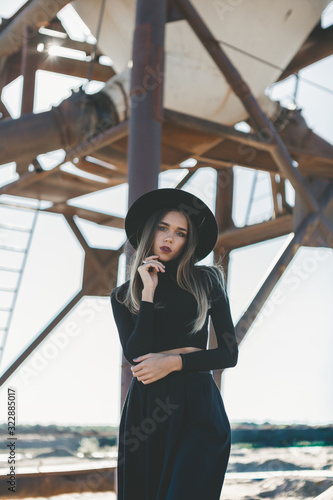 Photo A long haired blonde woman, dressed all in black, wearing a black fedora type hat, black sun glasses, distressed industrial silo