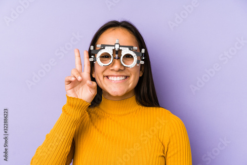 Fotomural Youn indian woman with optometry glasses showing victory sign and smiling broadly