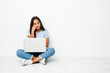 Young mixed race indian woman sitting working on laptop who feels sad and pensive, looking at copy space.