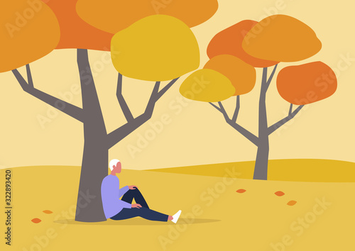 Fotografie, Obraz Young male character sitting under the tree, autumn outdoor leisure, hiking