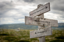 Environment, Economy And Society Text On Wooden Road Sign Outdoors In Nature.