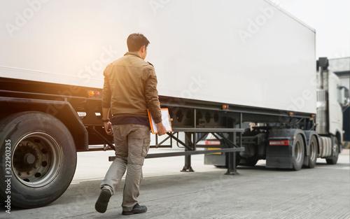 Obraz Truck driver holding clipboard inspecting safety vehicle maintenance checklist of semi truck - fototapety do salonu