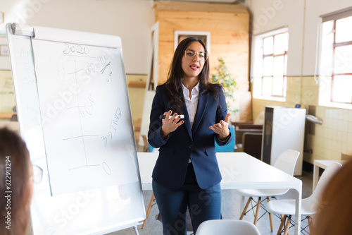 Concentrated business coach standing near whiteboard. Confident Asian manager doing presentation. Business training concept