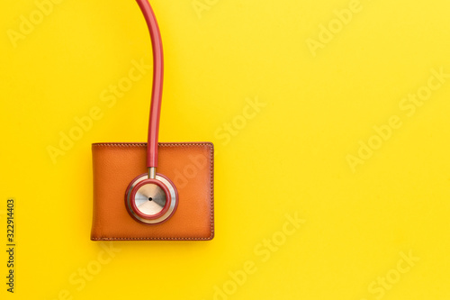 Fototapeta Doctor stethoscope and the new leather brown men wallet on yellow background. Budget for health check or money and financial concept obraz