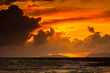 canvas print picture Sunset over sea surface, dark clouds.