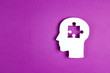 canvas print picture - Human head paper silhouette with a puzzle piece cut out on the purple background. Mental health symbol.