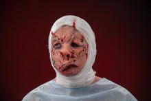 Crazy Zombie Horror Make Up. Person In Blue Madical Shirt And Bandaged Head. Scars, Deep Scratches Realistic Art Make-up. Head Is Re-banded Bandage, Beaten With A Stick. Banner For Halloween Party