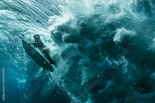 Underwater view of the woman surfer passing the powerfull ocean wave Wallpaper Mural