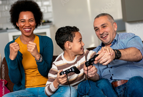 Fototapeta Smiling mixed race family enjoying time at home sitting on sofa in living room and playing video games. obraz na płótnie