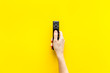 Leinwanddruck Bild - Watch TV concept. TV remote in hand on yellow background top-down copy space