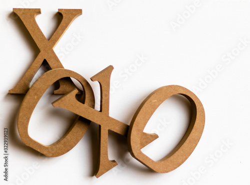 a friendship and love expression XO, XO a common frase of crude wooden letters at lower left corner, one letter overlaping the other on white and text space, minimalistic valentines day