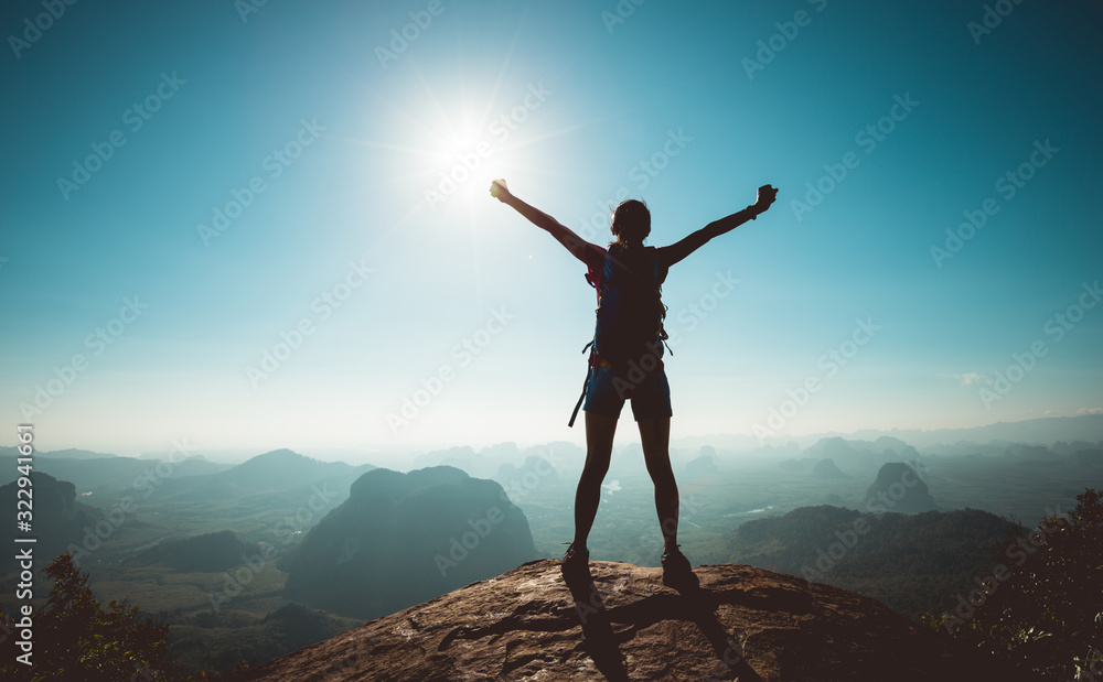 Fototapeta Cheering woman backpacker enjoy the view on sunrise mountain top cliff edge