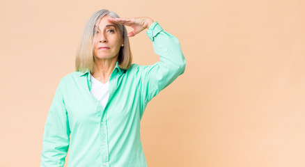 middle age cool woman greeting the camera with a military salute in an act of...