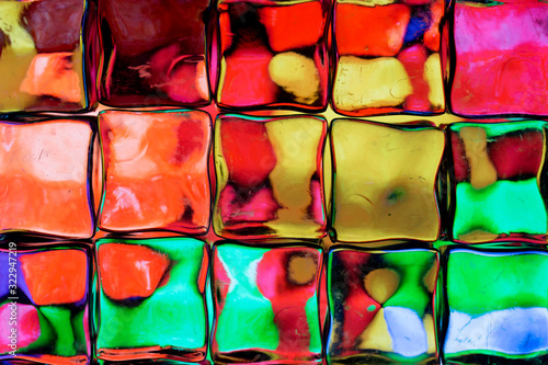 Obraz na plátně Abstract background of a colorful image distorted through a glass block wall