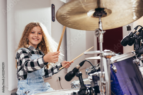 Fotografía young girl playing drums in music studio