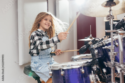 Fotografia young girl playing drums in music studio