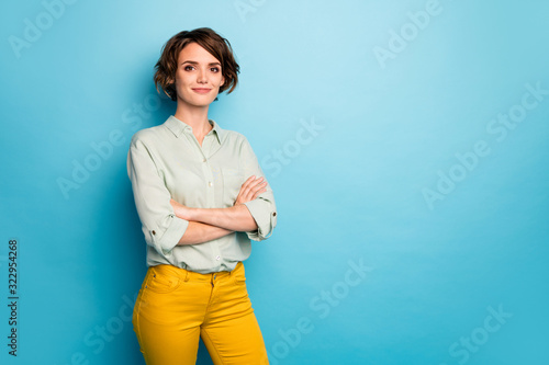 Photo of attractive pretty business lady short hairstyle friendly smiling responsible person arms crossed wear casual green shirt yellow pants isolated blue color background