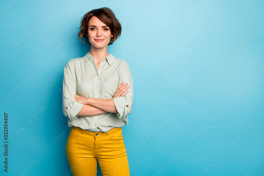 Fototapeta Photo of cool attractive business lady short hairstyle friendly smiling responsible person arms crossed wear casual green shirt yellow pants isolated blue color background