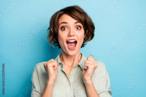 Fototapeta Closeup photo of funny excited lady raise fists screaming loudly celebrating money lottery winning wealthy rich person wear casual green shirt isolated blue color background obraz