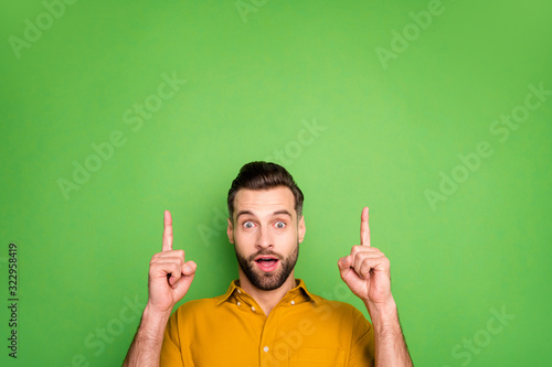 Fototapeta Close-up portrait of his he nice attractive funky amazed cheerful cheery guy in formal shirt pointing up attention like ad isolated on bright vivid shine vibrant green color background obraz