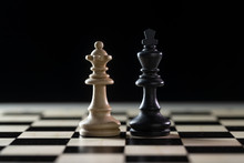 Two Chess Pieces, White Queen And Black King Side By Side On A Chessboard Against A Dark Background, Concept For Diversity, Gender Equality And Cooperation, Copy Space