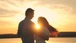 Loving man and woman dance in bright rays of sun on the background of the lake. Young couple dancing at sunset on beach. Happy guy and girl waltz in the evening in summer park.