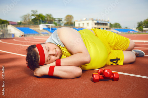 Obraz Fat lazy man sleeps tired lies on the track in the stadium. - fototapety do salonu