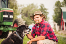 Portrait Of Farmer Smiling After Long Day Of Work, While Holding His Dog. Laurel, Montana, USA