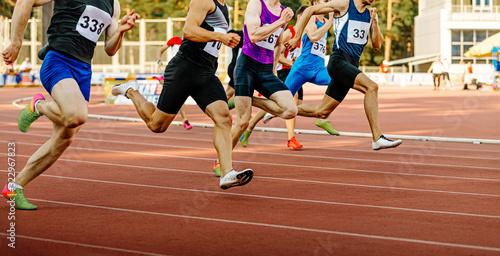 Obraz na plátně race group man runners sprinters run on track in athletics