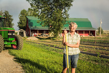 Portrait Of Female Farmer Smiling And Leaning On Shovel After Long Day Of Work. Laurel, Montana, USA