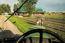 POV Of Farmer Driving With Tractor On Farm With Three Famers Looking On While Standing On Edge Of Field. Laurel, Montana, USA