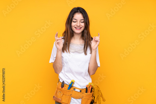 Photo Young electrician woman over isolated on yellow background laughing
