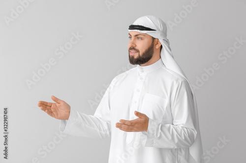 Photo Handsome Arab man showing something on grey background