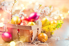 Easter Colorful Eggs In The Basket. Beautiful Colorful Yellow, Pink And Orange Color Eggs With Decorations And Spring Blossoming Flowers Over Bright Blurred Bokeh Background