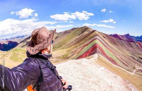 Adventure traveler guy taking selfie at Rainbow Mountain on Vinicunca mount during roadtrip travel experience in Peru - Wanderlust concept exploring nature wonders around the world - Warm vivid filter