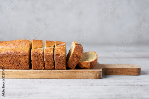 Fotografía Banana sweet bread sliced on  wooden cutting board