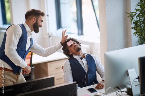 colleague making joke with a boss sleeping at work in office Canvas Print
