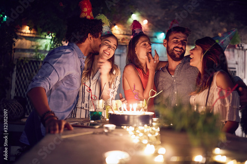 Fototapeta group of young friends celebrating a  birthday in the club with cake and candles at night.  birthday, party, fun, nighttime concept. obraz na płótnie