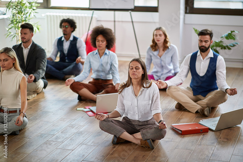 Obraz group of business coworkers meditating at work, sitting on the floor. modern, business, meditation concept - fototapety do salonu