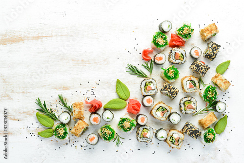 Fototapeta Set of tasty sushi and maki rolls on white wooden background. Japanese food. Top view. Free space for your text. obraz