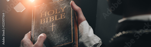 Photo partial view of catholic priest holding holy bible near confessional grille in d