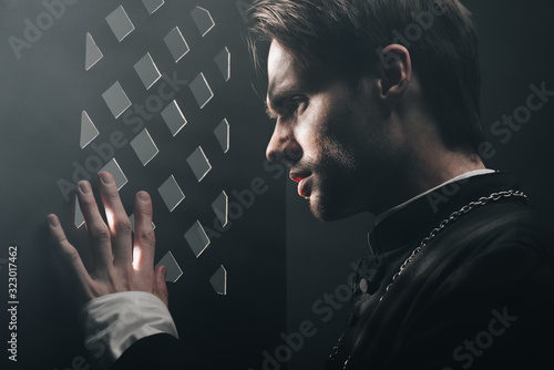 young tense catholic priest looking through confessional grille in dark with ray Canvas Print
