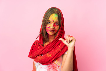 Young Indian woman with colorful holi powders on her face isolated on pink background proud and self-satisfied