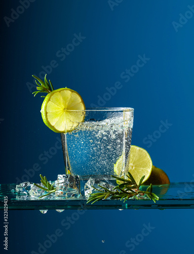 Obraz na plátně Cocktail gin-tonic with lime and rosemary on a glass table.