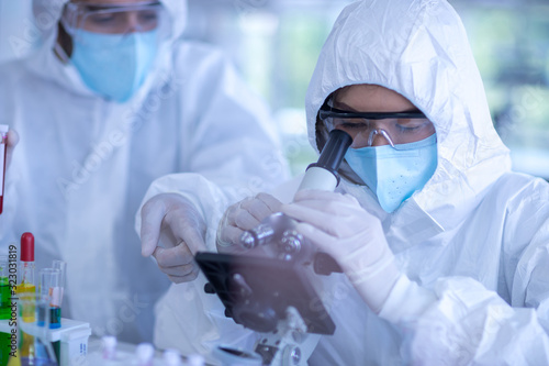 Fotografía A female scientist wearing a mask and looking through the microscope in the labo