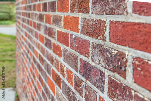 side angle view of rough red brick textured exterior wall