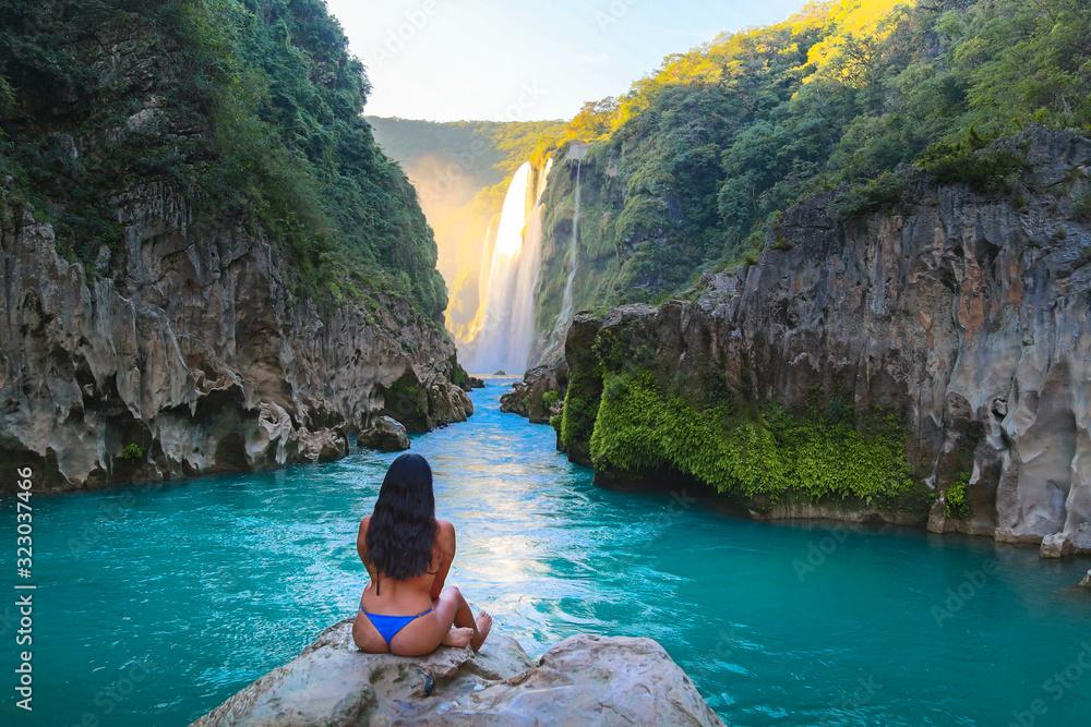 Fototapeta TAMUL, SAN LUIS POTOSI MEXICO - January 6, 2020:young women posing in River amazing crystalline blue water of Tamul waterfall