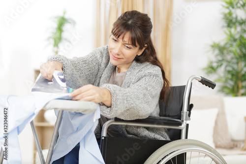 Fototapeta disabled woman during ironing at home obraz