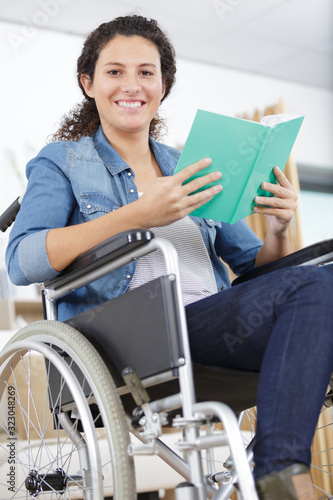Fototapeta young happy woman in wheelchair reading a book obraz