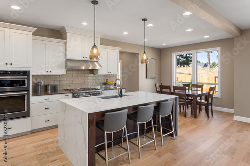Fototapeta Kitchen in new home with stainless steel appliances, island, and pendant lights. Shows dining area. obraz